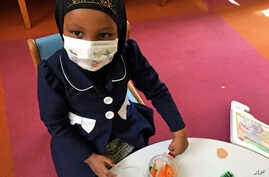 In this, May 2, 2017 photo, Amira Hassan plays in the waiting room at the specialty clinic at Children's Minnesota in Minneapolis. Hassan went to the hospital's clinic for a routine wellness check, but had to wear a mask to protect her from measles a