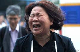 A family member of passengers aboard the sunken ferry Sewol cries after a pretrial hearing of crew members of the ferry at Gwangju District Court in Gwangju, South Korea, June 10, 2014.