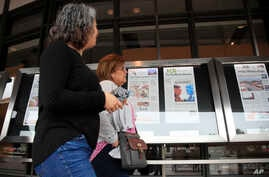 Newseum visitors browse newspaper front pages displayed outside the museum in Washington, June 11, 2018.