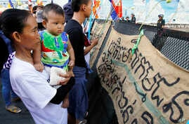 """Supporters gather in front of banners which read """" Please provide justice to land activists of Boeung Kak,"""" at a blocked main street near Phnom Penh Municipality Court in Phnom Penh, Cambodia, Friday, May 30, 2014. The court has convicted almost two"""