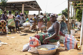 FILE - A vendor waits for customers to exchange her goods for other goods at the barter market in Togoville, Nov. 24, 2018. - Every Saturday on the northern shore of Lake Togo, some 65 kilometers (40 miles) east of the capital, Lome, Togoville runs a