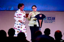 Indonesian Minister of Foreign Affairs Retno Marsudi, right, stands with Indonesian Minister of Marine Affairs and Fisheries Susi Pudjiastuti while speaking during the opening of the Our Ocean Conference in Bali, Indonesia, Oct. 29, 2018.
