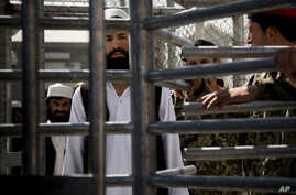 FILE - An Afghan prisoner waits in line for his release from Parwan Detention Facility after the U.S. military gave control of its last detention facility to Afghan authorities in Bagram, outside Kabul, Afghanistan, Monday, March 25, 2013.