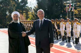 Iraqi President Barham Salih, right, and his Iranian counterpart Hassan Rouhani shake hands during an official welcome ceremony for Salih at the Saadabad Palace in Tehran, Iran, Saturday, Nov. 17, 2018.