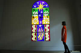 """An employee poses with a stained glass """"Christmas Eve"""" (Nuit de Noel), designed by Henri Matisse, and in collaboration with Paul Bony, at the Tate Modern gallery in London April 14, 2014.  An exhibition of Matisse paper cut outs """"Henri Matisse : The ..."""
