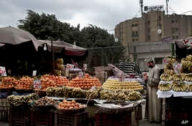 A fruit vendor checks an apple as he waits for customers in the Sayeda Zeinab neighborhood of Cairo, Egypt. Egyptians are cutting spending and trying to make it through the country's worst inflation in a decade under President Abdel-Fattah el-Sissi's