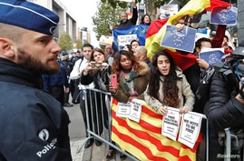 Demonstrators wave banners and flags as sacked Catalan leader Carles Puigdemont leaves a news conference at the Press Club Brussels Europe in Brussels, Belgium, Oct. 31, 2017.