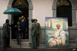 Sudan's President Omar al-Bashir, in doorway, walks past a portrait of late Ethiopian Prime Minister Meles Zenawi, a gift from another delegation, as he arrives to pay his respects to Meles' body lying in state at the national palace in Addis Ababa,