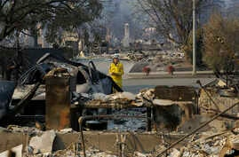 A California Fire Department forester inspects damage at homes destroyed by fires in Santa Rosa, California, Oct. 12, 2017.