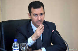 Syria's President Bashar al-Assad heads a cabinet meeting in Damascus, in this handout photograph distributed by Syria's national news agency SANA, Feb. 12, 2013.