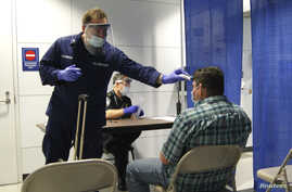 U.S. Coast Guard Health Technician Nathan Wallenmeyer (L) and Customs Border Protection (CBP) Supervisor Sam Ko conduct pre-screening measures on a passenger arriving from Sierra Leone at O'Hare International Airport's Terminal 5 in Chicago, Illinois
