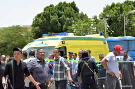 Police and people stand near the scene of a foiled suicide attack in Luxor, Egypt, June 10, 2015.  A suicide bomber blew himself up in the parking lot of Karnak temple in the southern Egyptian city of Luxor on Wednesday, security sources and witnesse