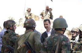 Syria's President Bashar al-Assad (C) chats with military personnel during his visit to a military site in the town of Daraya, southwest of Damascus, on the 68th anniversary of army day, in this handout photograph distributed by Syria's national news