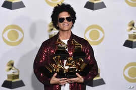 Bruno Mars poses in the press room with his awards at the 60th annual Grammy Awards at Madison Square Garden on Sunday, Jan. 28, 2018, in New York.