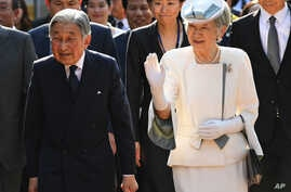 Japan's Emperor Akihito, left, and Empress Michiko walk into the compound of the memorial house of Vietnam's nationalist Phan Boi Chau (1867-1940) who campaigned for a strong relationship with Japan to gain Vietnam's independence, in the central city