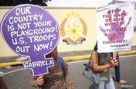 FILE - Protesters hold placards as they demonstrate against the ongoing negotiations between the U.S. and the Philippines in front of the military headquarters in Quezon city, metro Manila, Aug. 15, 2013.