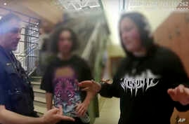 In this photo from body camera video, two Native American teenagers are questioned by Colorado State University campus police after they were pulled from a college tour, April 30, in Colorado. The teen's faces were blurred by the Colorado State Unive