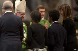 Pope Francis meets a family during a Mass in St. Peter's Basilica at the Vatican, Oct. 25, 2015. Pope Francis celebrated a final Mass to close out a historic meeting of bishops.