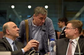 European Economic and Financial Affairs Commissioner Pierre Moscovici (L) chats with Greece's Finance Minister Euclid Tsakalotos (C) and European Commission Vice-President Valdis Dombrovskis during a Euro zone finance ministers meeting, May 24,  2016