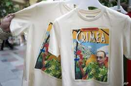 FILE - People examine T-shirts depicting Russian President Vladimir Putin and reading Greetings from Crimea at the biggest department store GUM in Moscow's Red Square.