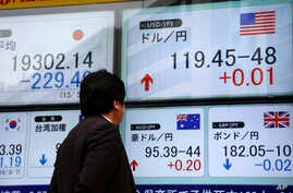 FILE - A man checks an electronic board for exchange rates in Tokyo, Japan, May 7, 2015.
