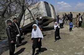 FILE - Schoolgirls walk past a damaged mini-bus after it was hit by a bomb blast in the Bagrami district of Kabul, Afghanistan.