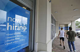 FILE - Shoppers walk past a now hiring sign at a Ross store in North Miami Beach, Florida, May 16, 2014.