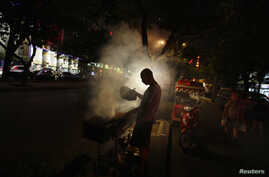 FILE - A man fans a grill while cooking kebabs at a roadside stall, in central Beijing.