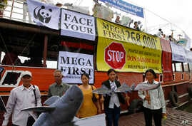FILE - Cambodian non-governmental organization (NGOs) activists hold a cut-out of Mekong dolphin, left, and cut-out of other species during a protest against a proposed Don Sahong dam, in Phnom Penh, Cambodia.