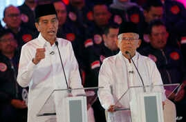 Indonesian President Joko Widodo, left, delivers a speech with running mate Ma'ruf Amin, right, during a televised debate in Jakarta, Indonesia, Thursday, Jan. 17, 2019.