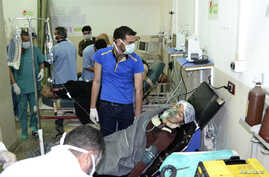 A woman affected by what activists say was a gas attack on the town of Telminnes breathes through an oxygen mask at Bab al-Hawa hospital, where she was transferred to, close to the Turkish border April 21, 2014. Chlorine gas attacks in Syria this mon