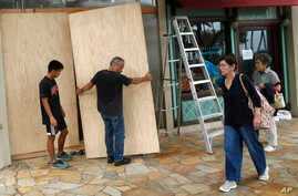 James Fujita, left, and Reid Fujita take down plywood boards that were to protect their store from Tropical Storm Lane along Waikiki Beach, Aug. 25, 2018, in Honolulu.