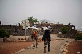 U.N. officers walk with equipment to observe areas in Syria's Quneitra province,  at an observation point on Mount Bental in the Israeli-controlled Golan Heights, Monday, June 22, 2015.