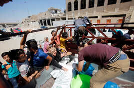 Citizens gather around a car that is distributing meat for the poor families in the old city of Mosul, Iraq, Aug. 22, 2018.