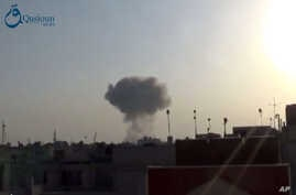 This image taken from video provided by the Syrian activist-based media group Qasioun News, which has-been verified and is consistent with other AP reporting, shows smoke rising from a Syrian government airstrike, in Douma, rural Damascus, Syria.