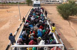 FILE - Migrants in a truck arrive at a detention center in Gharyan, Libya, Oct. 12, 2017.