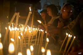 Christian worshipers light candles at the Church of the Nativity, traditionally believed by Christians to be the birthplace of Jesus Christ, ahead of Christmas, in the West Bank city of Bethlehem, Dec. 17, 2017.