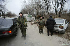 Pro-Russian separatists inspect cars at checkpoint in the Spartak area near the Sergey Prokofiev International Airport in Donetsk, Nov. 18, 2014.