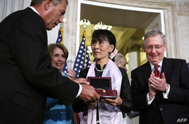 Burma's Aung San Suu Kyi (C) is presented with Congressional Gold Medal by Speaker of US House John Boehner as House Minority Leader Nancy Pelosi (2nd L) and Senate Minority Leader Sen. Mitch McConnell (R) look on Sept. 19, 2012