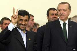 Iran's President Mahmoud Ahmadinejad flashes the V-sign for victory as Turkish Prime Minister Recep Tayyip Erdogan looks on after the Islamic republic inked a nuclear fuel swap deal in Tehran, 17 May 2010