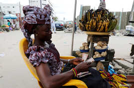 FILE: A woman selling plantain along a road counts the Nigerian naira near a currency exchange market in Ikeja district in Lagos, Nigeria, Aug. 12, 2017.