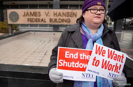 U.S. Internal Revenue Services employee holds signs in front of the federal building at a rally against the ongoing U.S. federal government shutdown, in Ogden, Utah, Jan. 10, 2019.