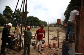 Construction workers are seen working in a new infrastructure at an expropriated golf field of the Caraballeda Golf & Yacht Club in Caraballeda, Venezuela, Feb. 20, 2018.