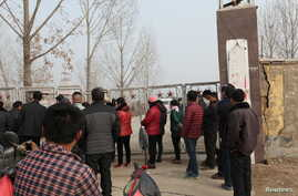 People stand outside a gypsum mine after it collapsed on Friday morning, in Pingyi, Shandong province, Dec. 25, 2015.