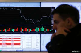 A man walks past an information screen on display inside the office of the Moscow Exchange in the Russian capital Moscow, March 14, 2014.