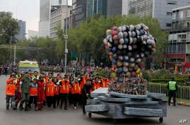 Rescue workers and volunteers that participated in rescue operations after the Sept. 19 earthquake, march behind a fist made out of safety helmets, as they lead the Day of the Dead parade on Mexico City's main Reforma Avenue, Oct. 28, 2017.