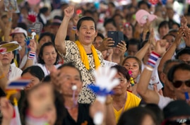 An anti-government protester raises her arm as she listens to a speech delivered by their leader Suthep Thaugsuban during a rally in Bangkok, Thailand, Saturday, May 10, 2014.