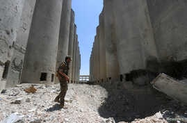 FILE - A Syria Democratic Forces (SDF) fighter walks in the silos and mills of Manbij after the SDF took control of it, in Aleppo Governorate, Syria.