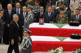 Lebanon's President Michel Suleiman pays his respects after placing honorary medals at the coffins of slain intelligence officer Wissam al-Hassan and his bodyguard Ahmed Sahyouni during an official ceremony to pay tribute their deaths, at the Interna