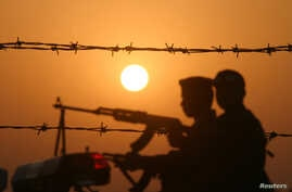 Iraqi soldiers conduct a patrol at sunset near the border with Kuwait in this file photo.